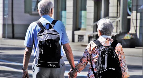 Grafika- Spacerujący seniorzy, trzymający się za ręce.