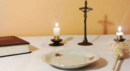 stół kolędowy. Świeczka, krzyż oraz talerz z wodą święconą.