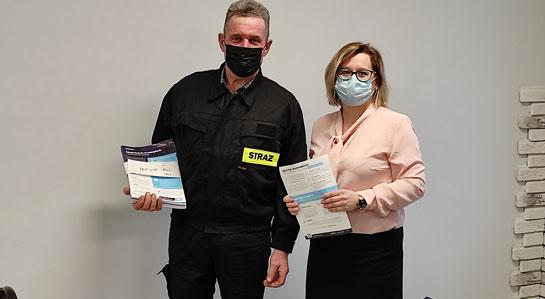 Na zdjęciu Katarzyna Czerwińska Gminny Koordynator ds. szczepień oraz druh Grędzicki prezentują ulotki